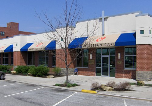 Photo showing the outside fo the Christian Care building - a red brick building with a white facade and blue awnings that feature the Christian Care logo of a cross in a heart